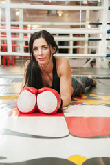 Fit woman with gloves at boxing ring