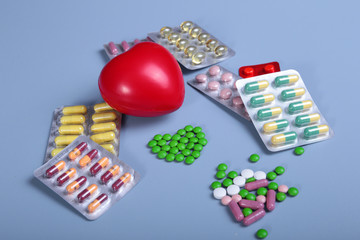 Packaging of tablets and pills on the table. Red heart