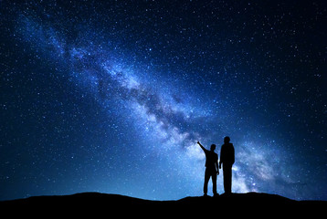 Milky Way with silhouette of men. Father and a son who pointing finger in night starry sky on the mountain. Night landscape. Silhouette of family on the background of beautiful galaxy. Space.