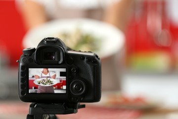 Girl holding salad in plate on camera screen. Food blogger concept
