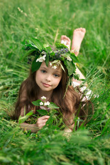 beautiful little girl in a white dress posing in the grass