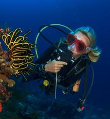 Woman scuba diver exploring coral reef