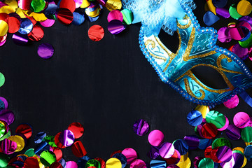 Top view of venetian masquerade mask and colorfull confetti.