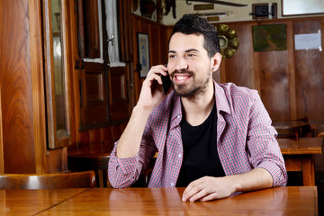Latin man talking on the phone in a cafe