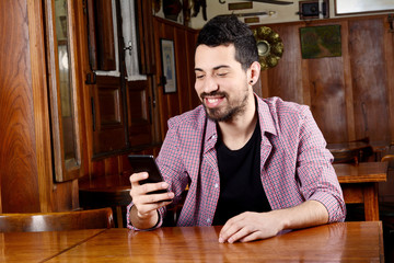 Latin man using his smartphone at a cafe.