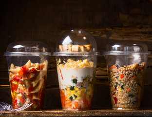Various vegetarian salads in plastic cups on dark wooden background. Healthy Take away lunch