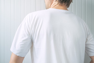 Casual adult male wearing blank white t-shirt from behind