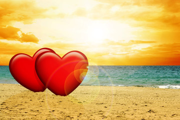 Two red hearts on the beach during sunset