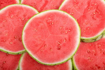 slices of whole watermelon cross section laid out to form a background of melon. Fresh summer fruit. view from above