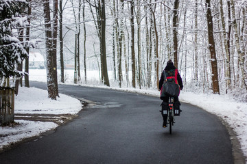 Woman cycling in the snow.