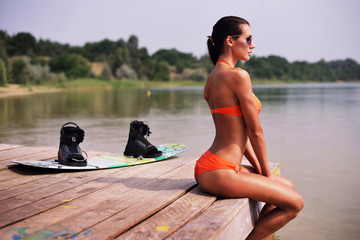 young beautiful woman on pier. Near wakeboard .