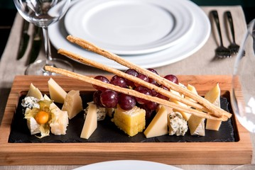 Assorted cheeses on a blackboard with a glass of wine in a restaurant. top view