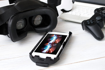 Smartphone laying on desk and prepared to play with VR googles.