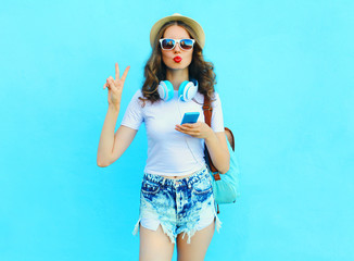 Pretty cool woman listens music and using smartphone over colorf