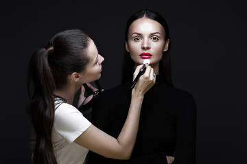 Two beautiful girls on a photo shoot to apply makeup to the face. Beauty fashion model. Photos shot in studio