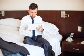 Businessman reading the news on a tablet