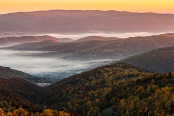 cold autumn morning fog on red hot sunrise in the Carpathian mountains