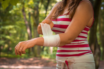 Woman applying bandage on her hand after injury