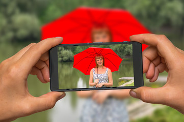 Taking photo of lady with red umbrella with mobile phone