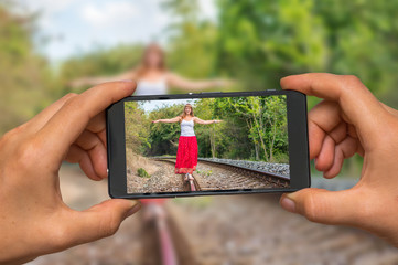 Taking photo of lady walking on railway with mobile phone