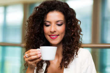 Portrait of happy brunette drinking coffee