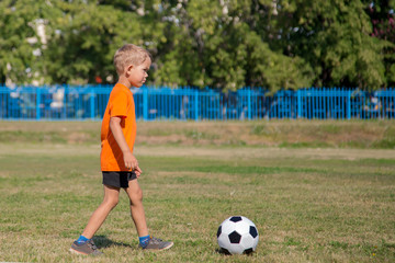boy in orange t-shirts go to the soccer ball