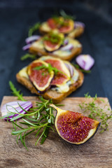 Baked toasted of dark bread with blue cheese and figs served on cutting board.