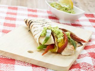 delicious wrap tortilla with spicy chicken vegetables guacamole