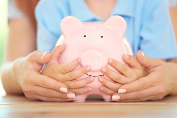 Savings concept. Mother and little boy hands holding piggy bank, close up