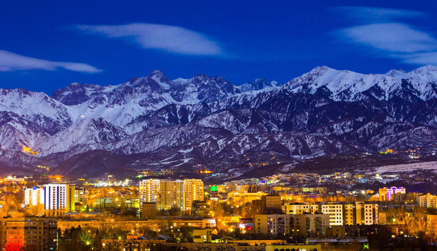 Almaty and mountains under the moonlight