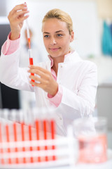 Laboratory chemist full test tube with long pipette