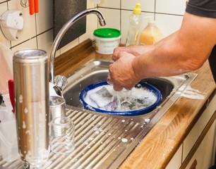 Men hands wash dishes