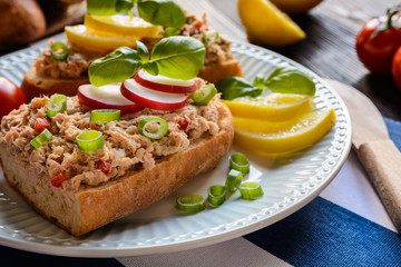 Slices of baguette with tuna spread, red pepper and green onion