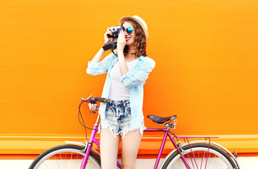 Fashion pretty woman with retro camera and bicycle over colorful