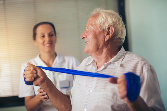 Senior man doing exercises using a strap to extend