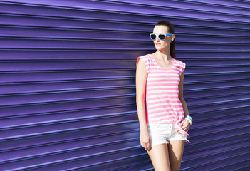 Female fashion model posing against colorful background.