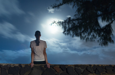 Young girl sitting at night watching the full moon.