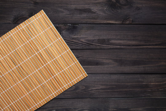 Bamboo mat on wooden table, top view
