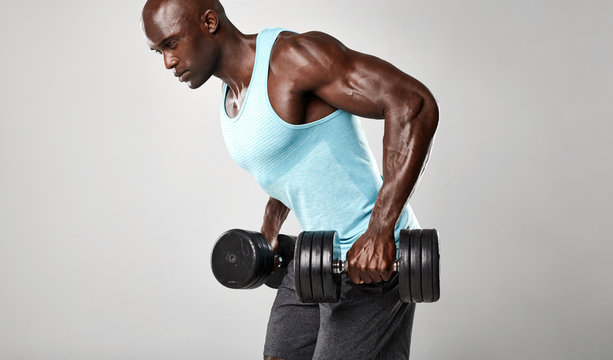 Healthy african man exercising with dumbbells