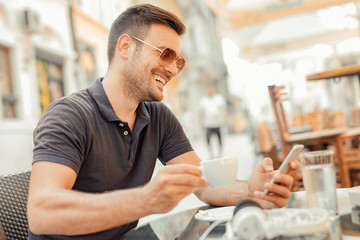 Young man using smart phone in cafe