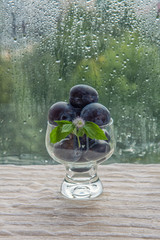 On the street it is raining. Drops on the window glass. On the table is a glass vase with plums. Fresh fruit in the vase. Healthy eating