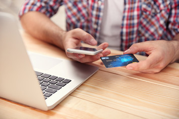Man hands using credit card and phone for online shopping
