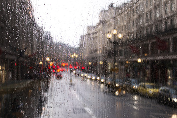 blurred view of road traffic in London on a rainy day through the bus window. raindrops on the glass window of the bus