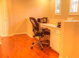 Irvine, CA, USA – August 19, 2016: Small Office nook desk in a loft with a desk, chair, recessed lighting, wood floors and feng shui decor.