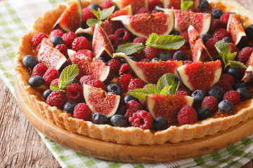 Summer cake with fresh figs, raspberries and blueberries close-up. horizontal