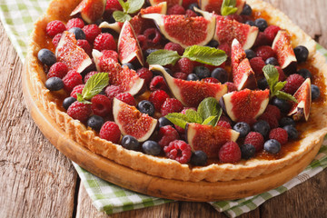 Delicious pastry: tart with fresh figs, raspberries and blueberries close-up. horizontal