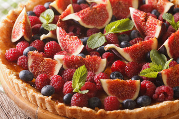 tart with fresh figs, raspberries and blueberries macro. horizontal