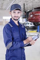 Arabic mechanic holds clipboard in workshop