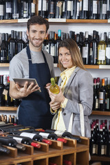 Salesman Holding Digital Tablet While Customer With Wine Bottle