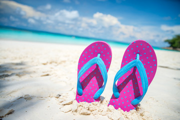 Pink beach flip flop on white sand beach
